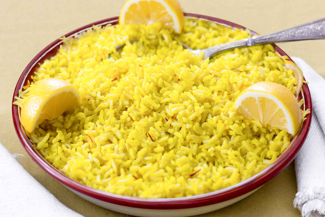 Shallow red-rimmed bowl with Saffron & Lemon Infused Basmati Rice garnished with 3 lemon wedges