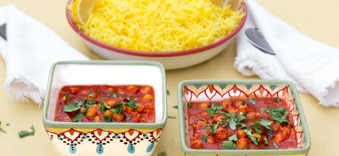 Two hand-painted bowls of Moroccan Inspired Warm-spiced Chickpeas with a bowl of Saffron & Lemon Infused Rice behind