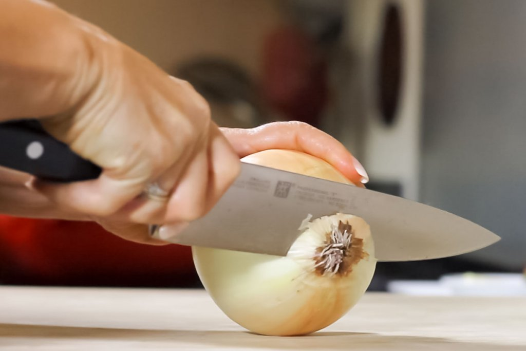 Using the Henckels Professional Chef Knife, cut the root end off leaving enough root to hold the onion together