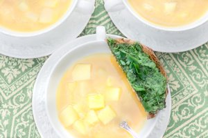 Three white Wedgwood bowls of oil-free vegan Fresh Springtime Garlic Soup with a parsley & cilantro pesto toast