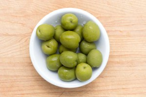 Small white plate of whole Castelvetrano Olives