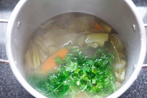 Sock post with mirepoix vegetable stock and fresh herbs added after simmering