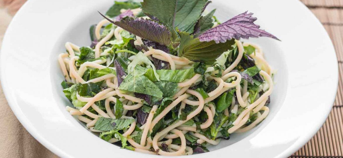 Large white rimmed bowl with Asian Herbs & Noodles, garnished with whole purple and green perilla leaves.