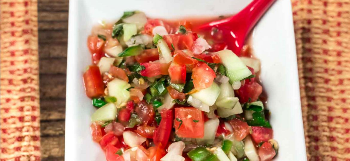 Small square white bowl Garden Salsa Fresca is a naturally sos free salsa fresca with fresh tomatoes, white onion, cucumbers, cilantro, burst of lime juice and a little kick from the jalapeno pepper. with a red spoon.