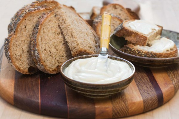 Luscious Oil-free Vegan Butter swirled in a small bowl served with whole grain bread on a wooden board