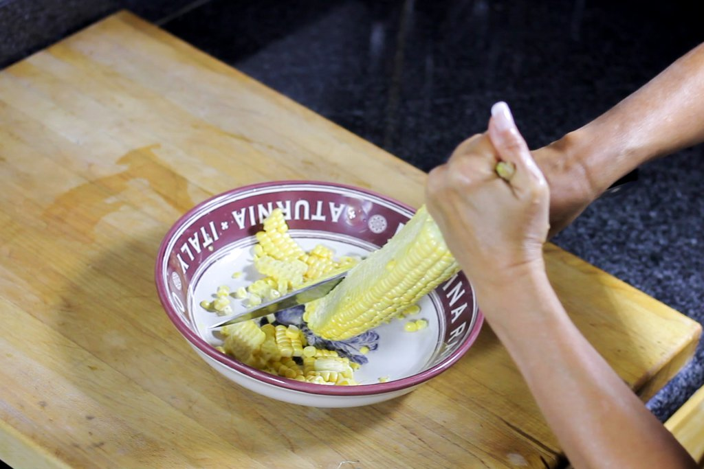 Removing corn kernels with a chef knife into a shallow bowl