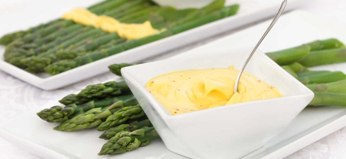 Silky smooth oil-free vegan hollandaise in a square white bowl served with blanched asparagus on white rectangular plates.