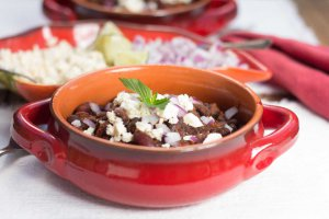 Red-glazed terracotta casserole serving dish with Chile Bean ChiliOil-free Vegan Chile Bean Chili and a chile pepper-shaped dish with tangy bites, lime wedges and diced red onion behind.