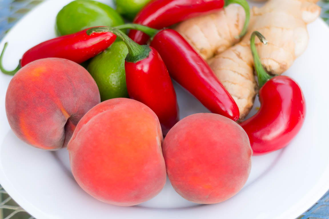 Peaches, red Jalapeno peppers, limes and ginger on a white plate