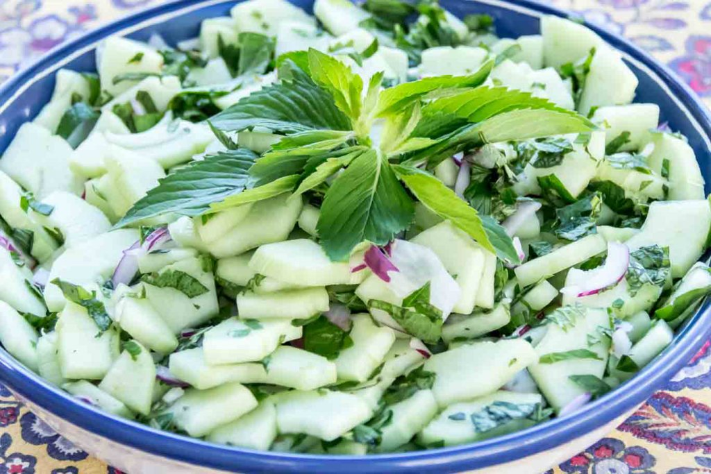 Blue rimmed shallow bowl with Cool Peppermint and Cucumber Salad garnished with fresh whole leaf peppermint in the center.