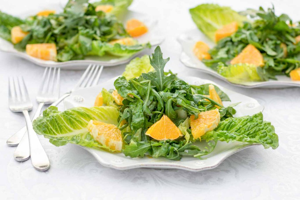 Three white scalloped plates with Whole Orange Balsamic Arugula Salad on a white tablecloth.