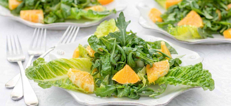 Three white scalloped plates with Whole Orange Balsamic Arugula Salad on a white tablecloth.