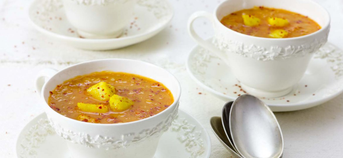 Three white wedgewood cups of Red Lentil Soup with Carrot and Ginger garnished with spice potatoes and a sprinkle of Aleppo pepper.