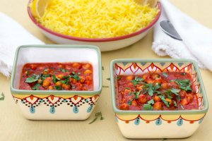 Two square hand-painted bowls with Moroccan Inspired Warm-Spiced Chickpeas and a shallow bowl with saffron rice in back.