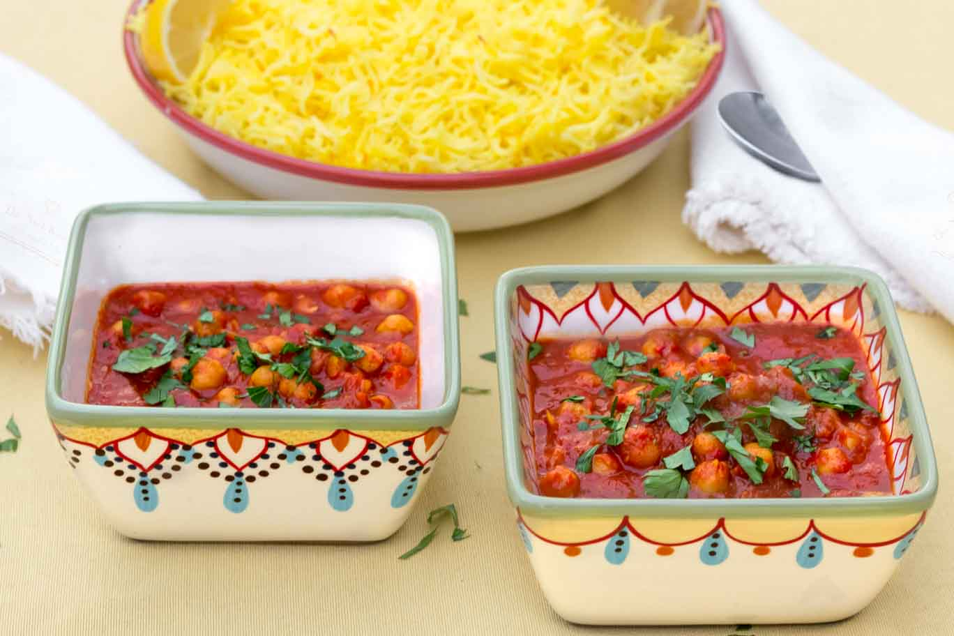 Two square hand-painted bowls with Moroccan Inspired Warm-Spiced Chickpeas and a shallow bow with saffron rice in back.
