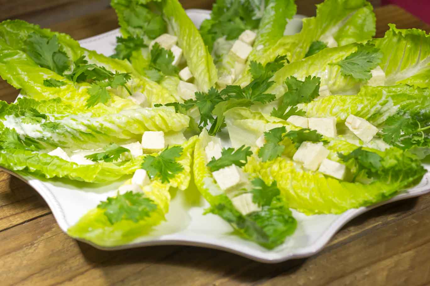 Scalloped white serving platter with Romaine Salad Boats.