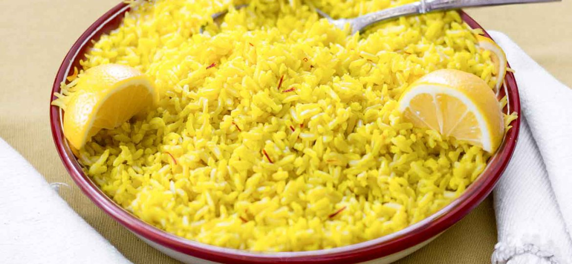 Shallow bowl with Saffron & Lemon Infused Basmati Rice garnished with 3 lemon wedges