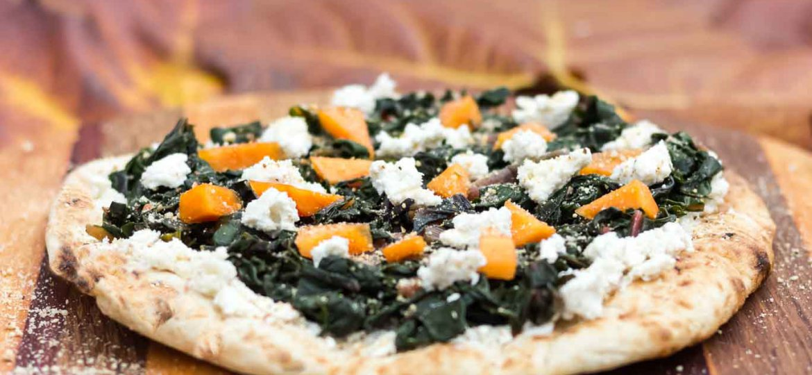 Swiss Chard & Creamy Almond Ricotta Pizza on a wood serving board.