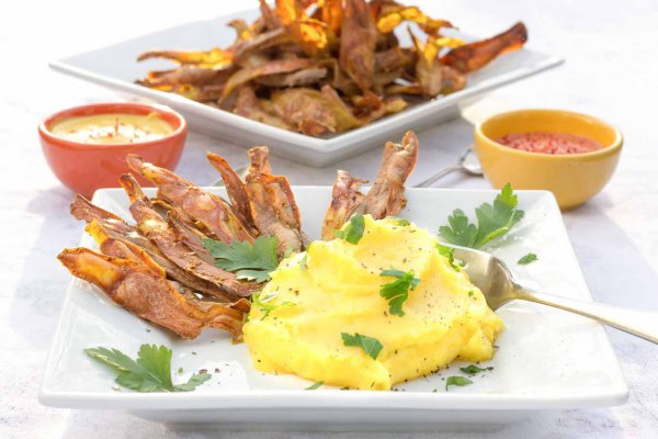 White square plate with coil-free potato skin crisps and golden mashed potatoes. Two condiment dishes behind and a platter of the oil-free potato skin crisps.