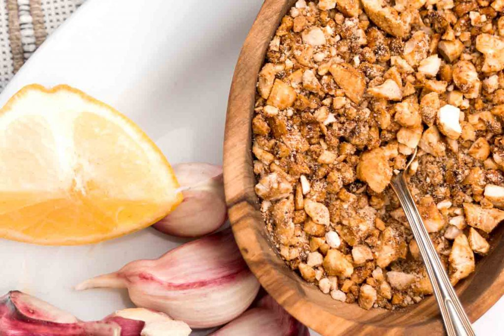 Salt-free Cashew Spice Blend in a small olivewood bowl on a white plate with garlic cloves and a lemon wedge