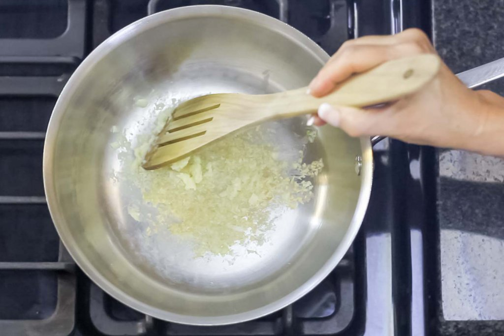 Making a layer of grated garlic on tha pan surface with an olivewood flat spatula