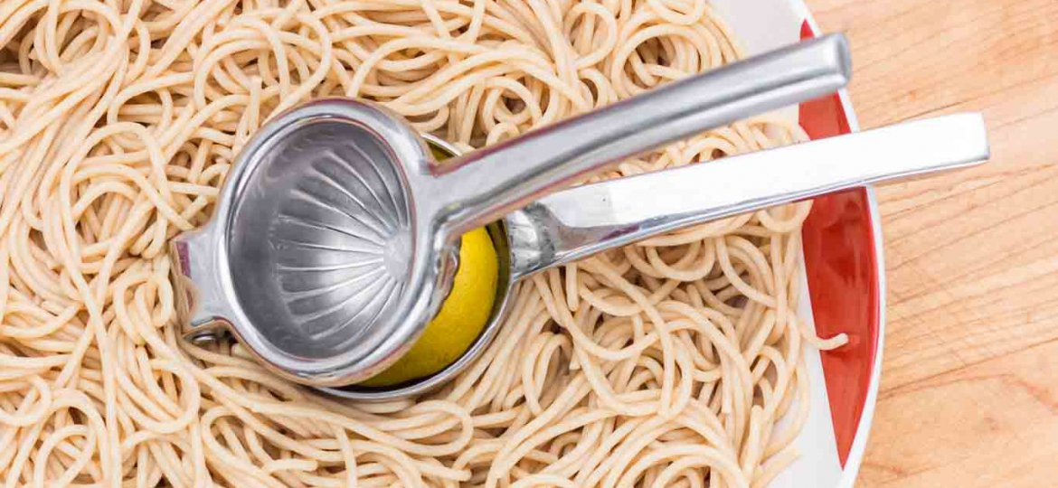 Squeezing lemon juice with a Stainless Steel Lemon Squeezer over a bowl of pasta.
