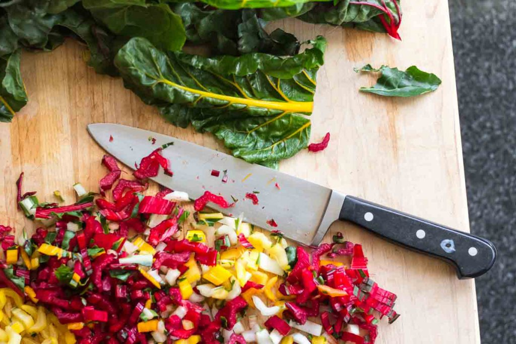 Boos Board in use with chopped rainbow Swiss Chard stems and a chef knife.