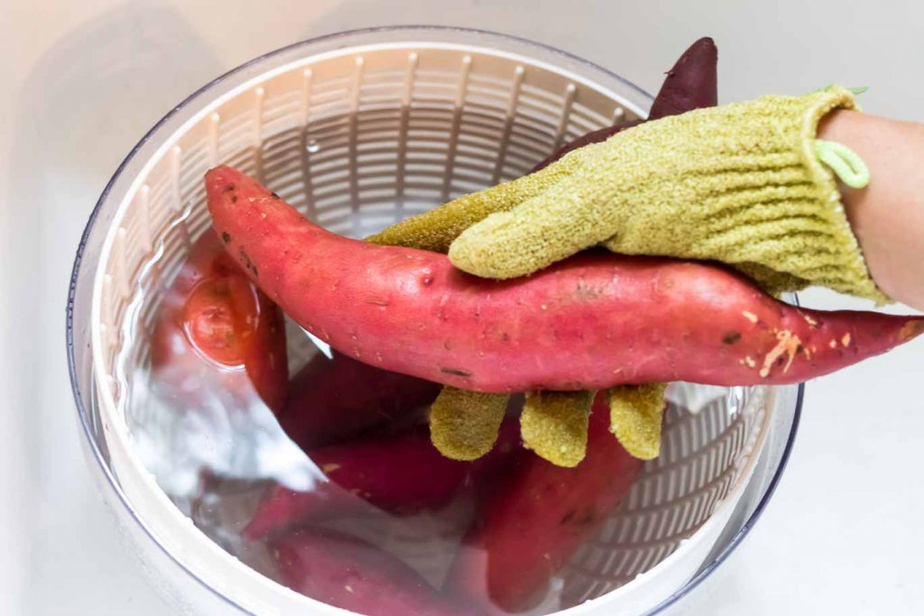Scrubbing a sweet potato with a vegetable scrub glove over a salad spinner bowl of water
