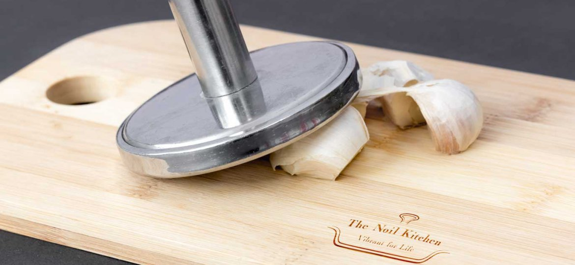 Garlic cloves on a cutting board. Tap the garlic cloves to remove the outer paper skin