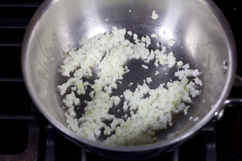 Saucier pan with onions sauteeing until starting to turn translucent