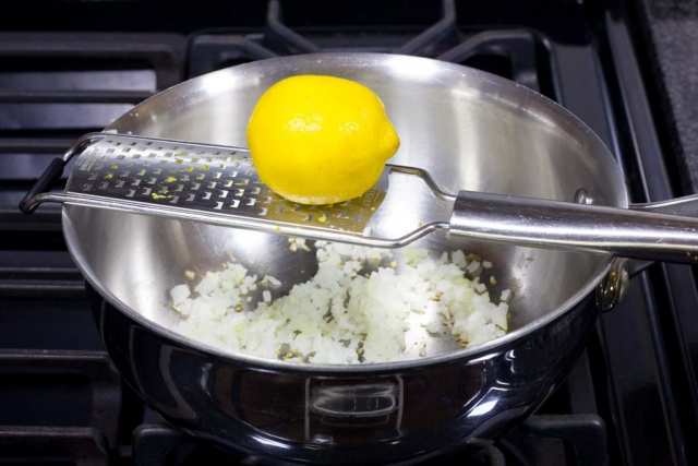 Zest the yellow part of the lemon skin with a micro-plane grater right into the pan with the onions.