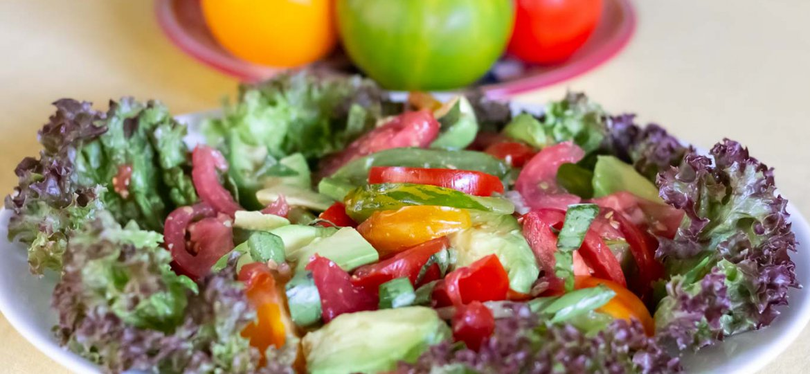 Summer Tomatoes & Avocado Salad on bed of red leaf lettuce (Lollo Rosso) with whole tomatoes behind.