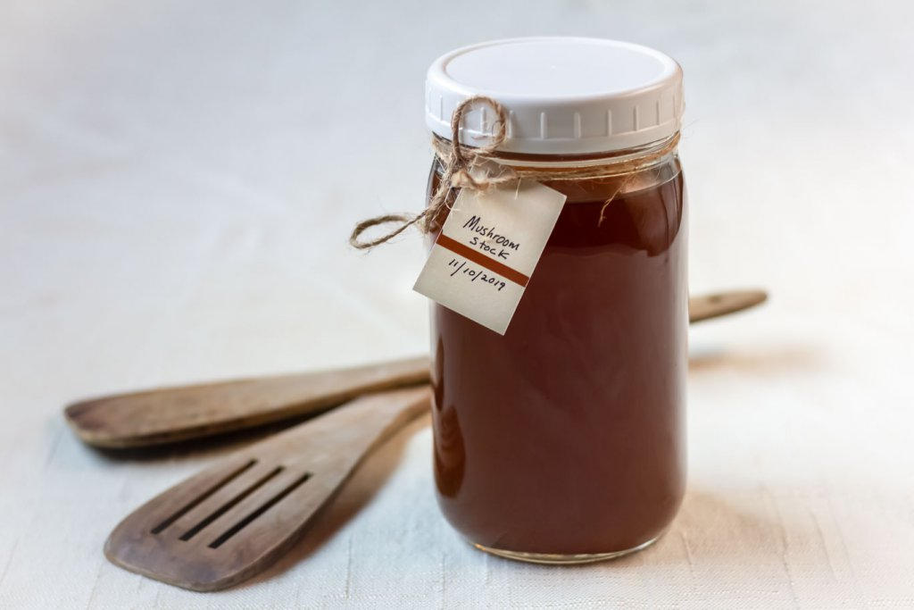 Mason jar filled with Caramelized Mushroom Stock, and a date and title tag on the jar next to 2 wooden spatulas o