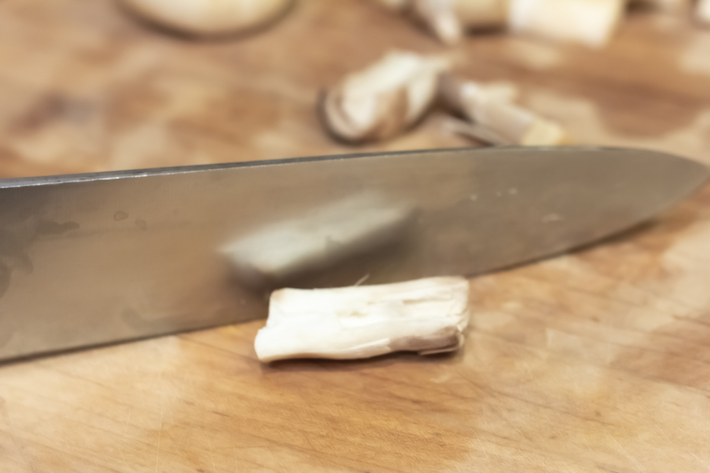 Cut the mushroom stem in half lengthwise to give a flat surface.