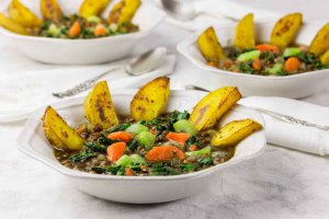 3 white bowls of Mirepoix Mirepoix lentil soup with vibrant vegetables andwith roasted potatoes