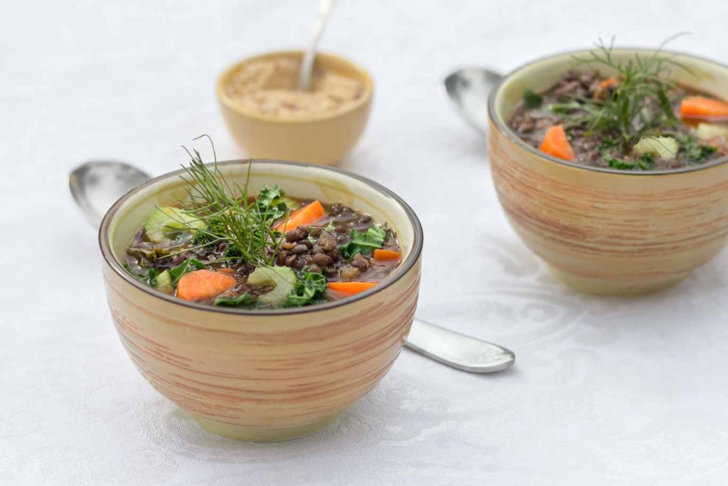 Two ceramic bowls of Mirepoix lentil soup garnished with fennel frons and a small bowl of salt-free spiced cashew blend behind Mirepoi