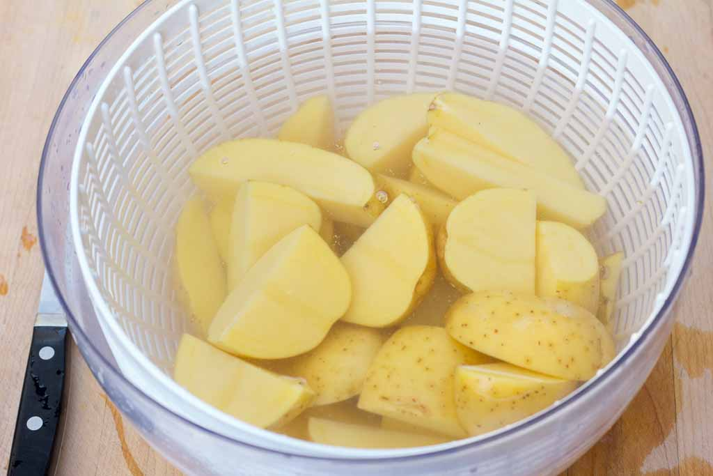 Salad spinner bowl filled with clean water to rinse the cut potatoes