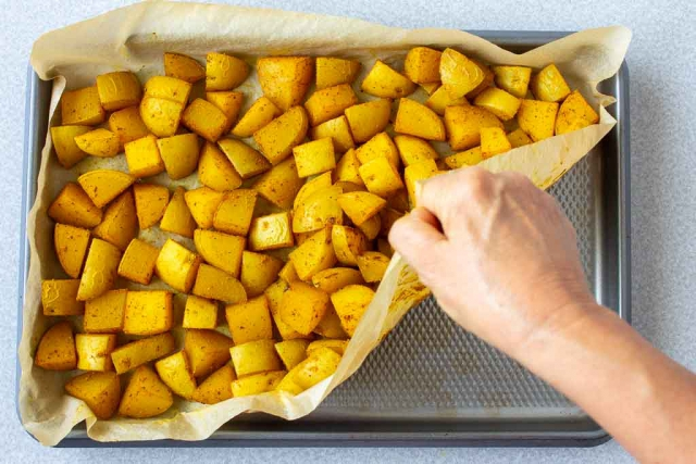 Lifting the parchment paper corner will help release the potatoes