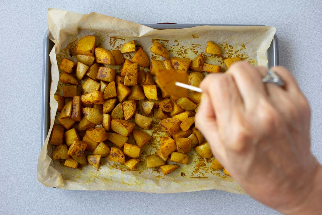 Check if the potatoes are done by pushing a toothpick through a couple of pieces