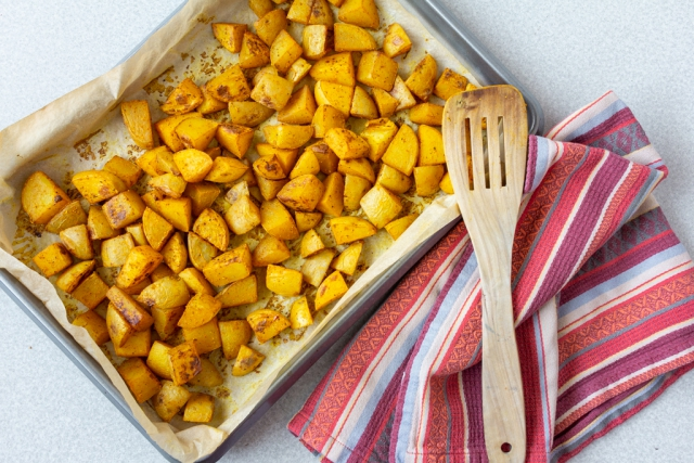 turmeric spiced oil-free roasted potatoes on a baking sheet with a teal towel and wooden spatula on the side