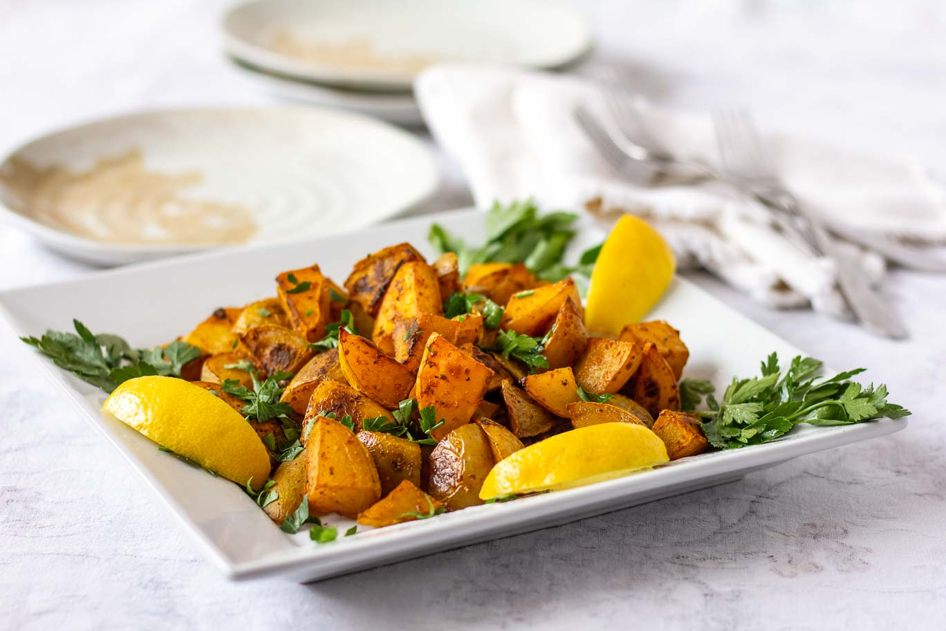 Square white plate with Turmeric spiced Oil-free Roasted Potatoes garnished with 3 lemon slices and parsley