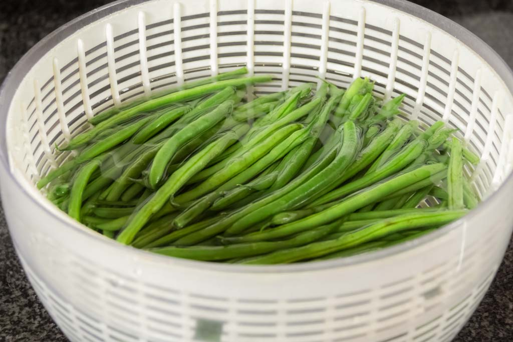 Green beans in a salad spinner filled with water to wash