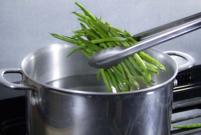 Green beans held with tongs dropping into boiling water