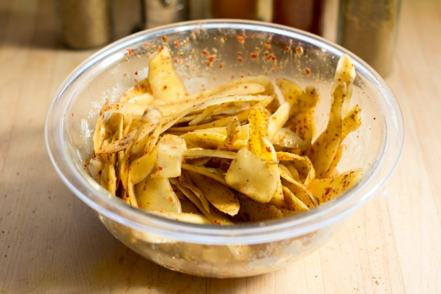 potato peels in a glass prep bowl tossed with spices and vinegar