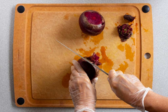 Cutting the stalk off beet with a chef knife on a cutting board