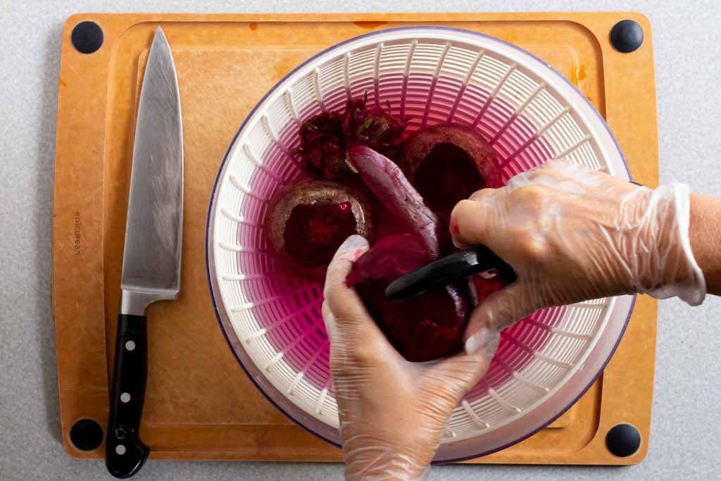 Peeling the skin off a red beet over the salad spinner bowl of water