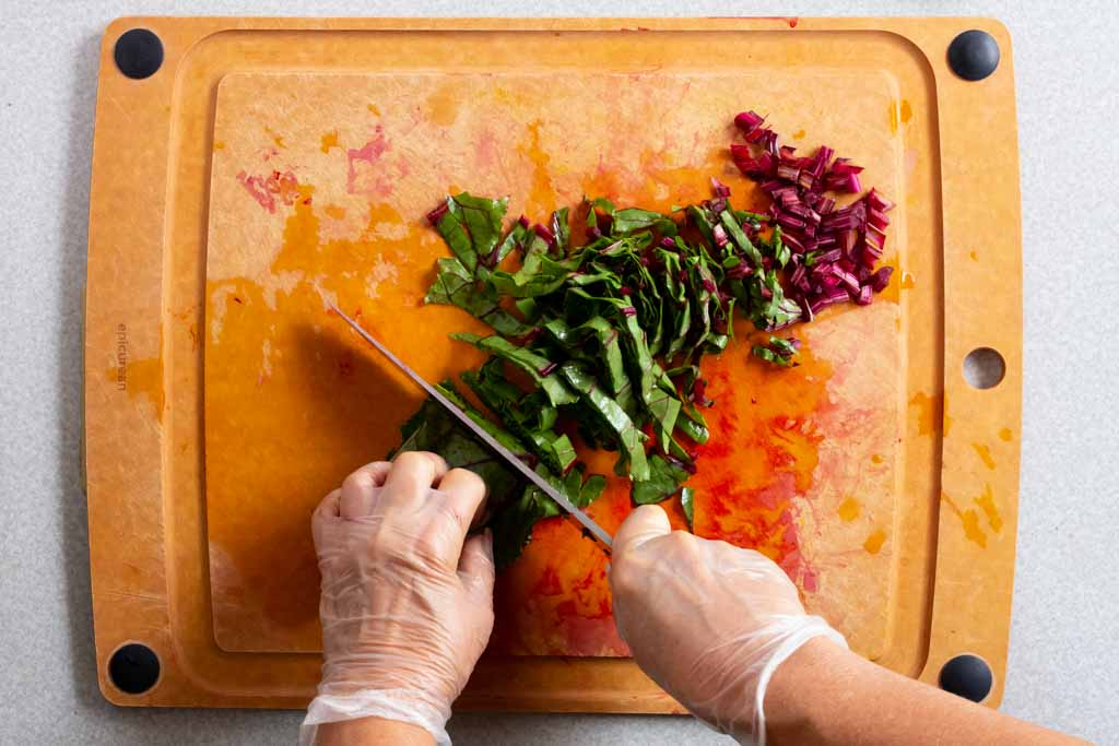 Slicing beet stalks and greens on a cutting board
