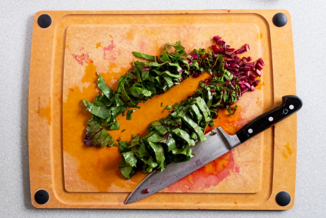 Beet greens cut lengthwise on a cutting board with a chef knife