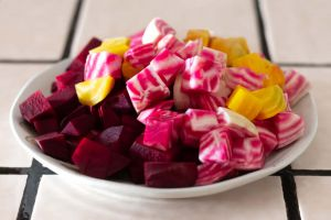 Mixed raw diced beets, Chioggia, Detroit red and Golden beets, on a round white plate
