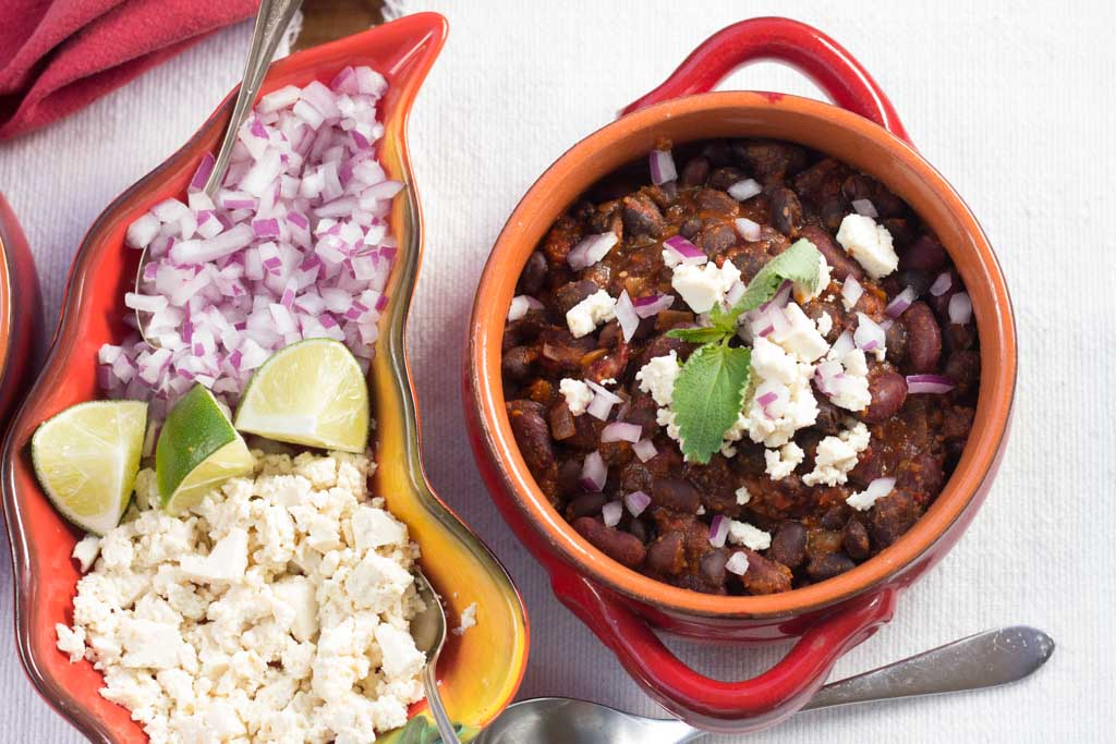 15 Garnishes: Red and yellow dish with red onion, vegan feat and lime slices and bowl of Chile Bean Chili